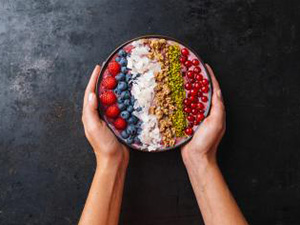 Woman hands hold a Healthy breakfast bowl, wirh blueberry smoothie with, raspberry, blueberrys, coconut, nuts and currants toppings : Stockfoto oder Stockvideo und Fotos, Bilder, Stockmedien von rcfotostock | RC-Photo-Stock